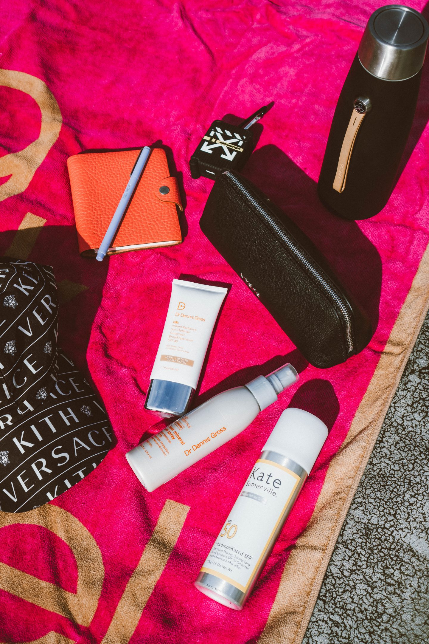 Science Forward Beauty Products x Dr. Dennis Gross Instant Radiance Sunscreen, mineral sun spray, livana silk slip bottle, hermes notebook, kith versace hat